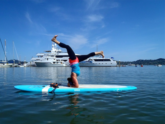 Instructor Leigh Claxton demonstrates a Sirsha-asan, Sausalito harbor.  Photo courtesy of OnBoard SUP