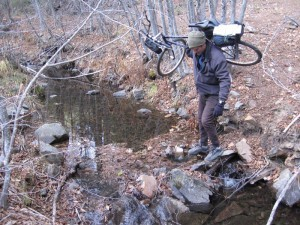 "Andy Padlo carries his bike over a rough section of the ""road."""