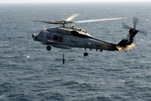 Environmentalists and animal advocates contend that Navy sonar testing in the ocean is harming whales and other marine wildlife and are calling on the Navy to curtail such training and testing exercises accordingly. Pictured: A Navy helicopter lowers a sonar device into the ocean. Photo: Official U.S. Navy Imagery