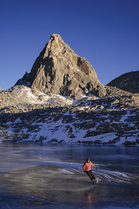 Brent Taylor leans into a turn on a frozen lake in Dusy Basin, with Isosceles Peak in the background. Photo: John Dittli