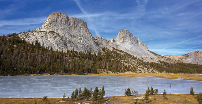 Matthes Crest looms above Cathedral Lakes as Rob and Laura Pilewski enjoy ice-skating in northern Yosemite. Alpine ice-skating allows visitors to experience places with which they are deeply familiar from a whole different perspective. Photo: John Dittli