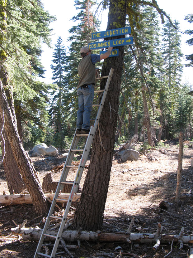 A volunteer installs signs on trail system that was marked by Snowlands Network.