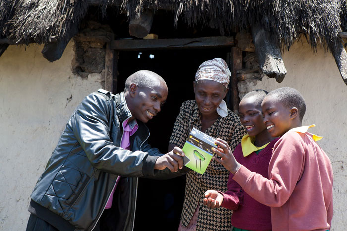 A SolarAid entrepreneur distributes solar lights in his community. Through local programs like this one, SolarAid has distributed over 1 million lights in Africa thus far. Photo: SolarAid