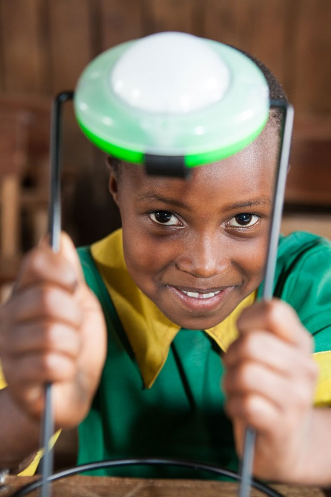 An African child displays a simple solar light that  provides a cheap, clean alternative to kerosene.  With this technology children are not only healthier, but can better study at night, giving their future  even greater opportunities. Photo: SolarAid
