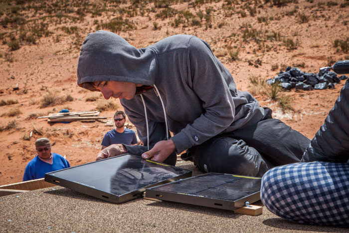 Alex Honnold installs solar panels on the roof of a Navajo home deep in Monument Valley during the kick-off of the Northern Navajo Solar Entrepreneurs Project. Photo: GoalZero