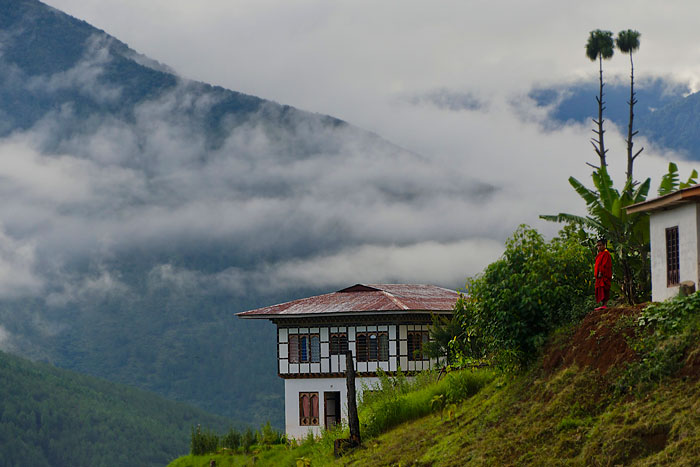 A monk assesses the  morning mist at a monastery above Punakha, Bhutan. Photo: Terri Schneider