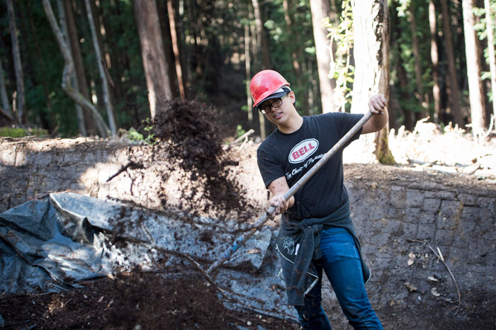Distributing duff to the center of a well-crafted berm. Re-naturalizing is a crucial component of responsible trail construction. (Josh Sawyer/BRG Sports)