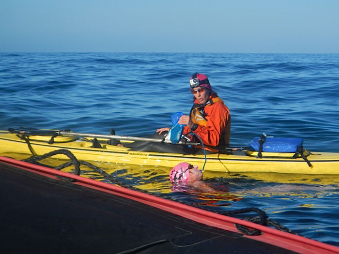 Kayak support crew feeding Patti during her swim.