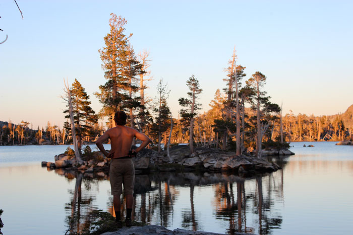 Santos stands near one of the dozen tiny islands on Middle Velma Lake.