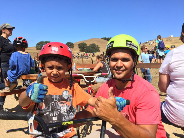 BMX athlete and announcer Al Roybal gives a big thumbs up with son Julian.