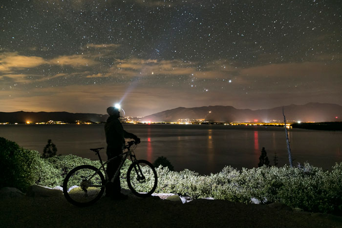 A rider rests under a blanket of stars (David Clock Photography).
