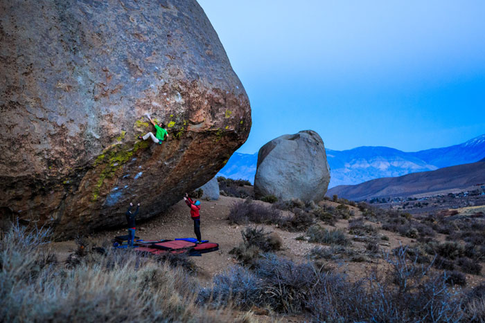 Matt Segal works out the committing reach move to pull the lip on Evilution Direct, a massive highball boulder problem on the Grandpa Peabody boulder of Bishop's Buttermilk (Jeff Diekes).