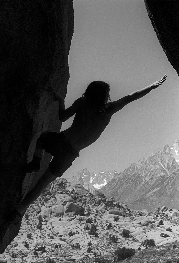 Roger Schley strains toward the lost-to-history Iron Cross move to top out on Inner Sanctum, the Cave Boulder (Gordon Wiltsie).