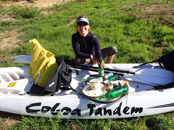 A paddler proudly displays the trash she cleaned from the river (David Casterson).