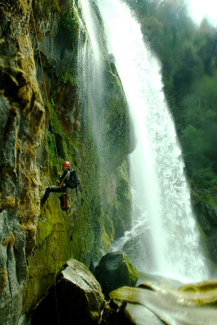 Amanda Guenther rappelling down a mossy waterfall.