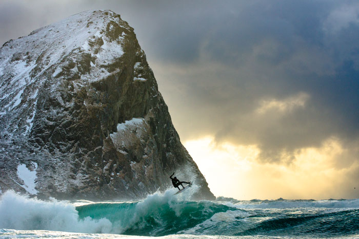 Surfing in 40 degree water in the Lofoten Islands, Norway. With towering mountains and the dramatic sun seeping color in from behind the clouds, Dane Gudauskas, does his best to stand out amidst the untamed Arctic coastline.