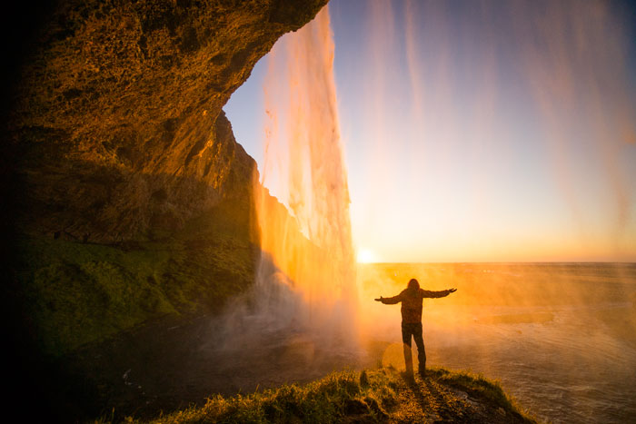 Soaking up the last minutes of sunlight behind the Seljalandsfoss waterfall in Iceland, 2014.