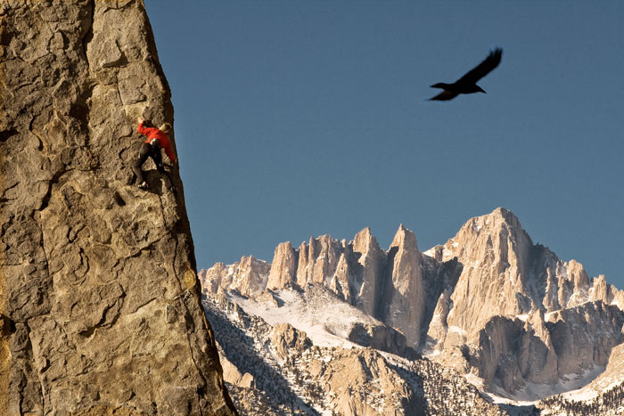 A raven keeps an eye on Caroline Schaumann as she climbs the Shark Fin in the Alabama Hills.