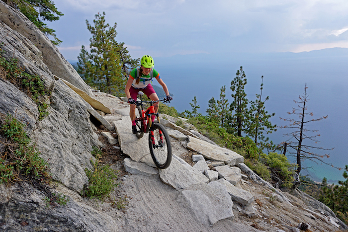 A female mountain biker on the Flume Trail above Lake Tahoe, with a beautiful view of the lake.