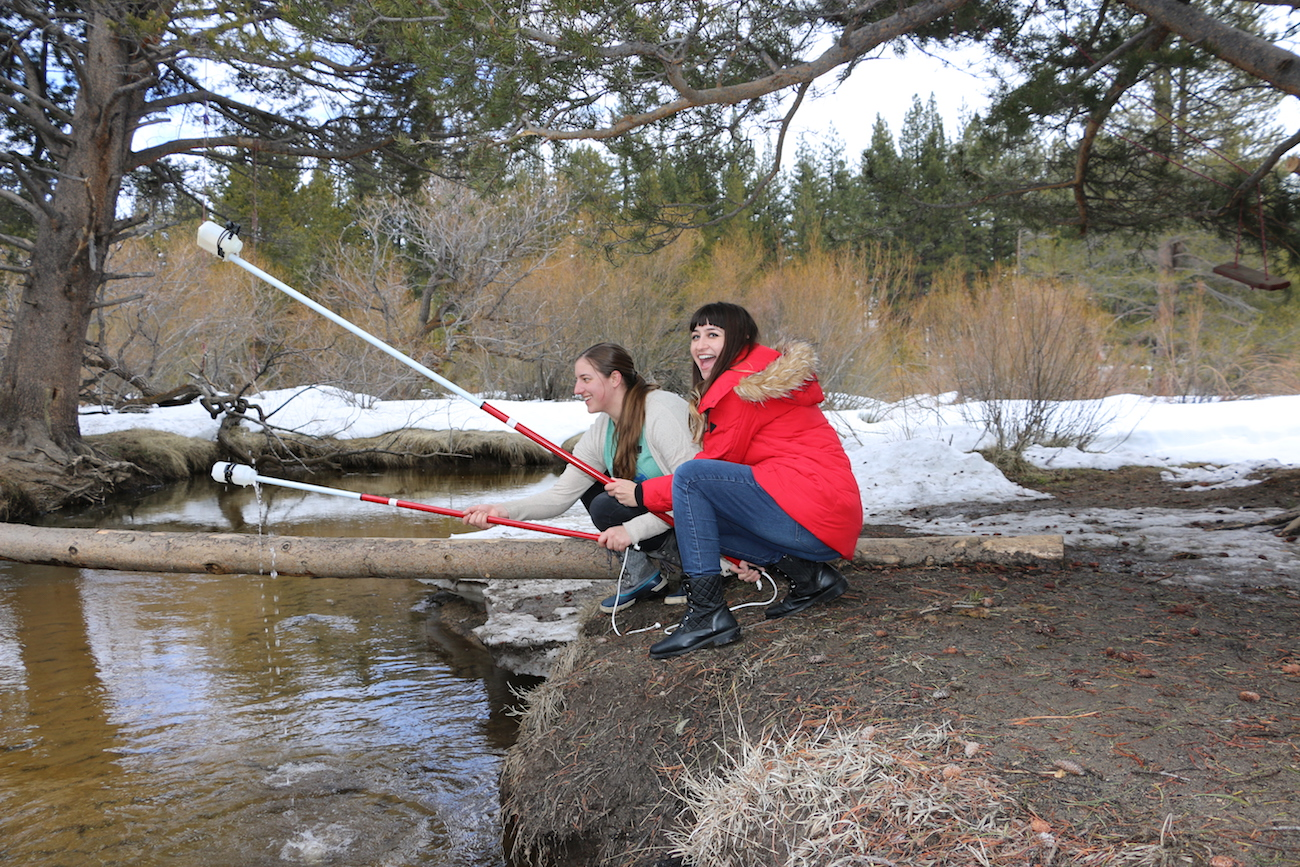 Two girls monitoring pipes and drains. Keep Tahoe Blue